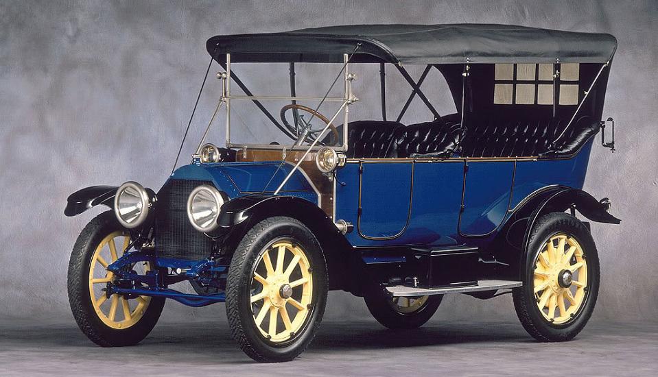 """<p style=""""text-align: center;""""><strong>Cadillac Touring Edition. </strong>Основанная Генри Фордом марка Кадиллак откололась от империи под давлением финансовых покровителей компании и Cadillac Touring Edition стал первым опытом самостоятельного создания автомобиля. Для своего времени он стал безумно роскошным, например, в нем был установлен электрический стартер и больше не приходилось крутить ручку на холоде. Проблема ручного стартера на момент начала производства Cadillac Touring Edition стояла очень остро — внезапно запустившийся двигатель мог переломать автомобилисту руки и такие случаи были далеко не редки. С другой стороны, внедрение электрического стартера сделало автомобили более доступными для женщин. Именно за руль Кадиллака впервые уселась женщина и этот факт был широко освещен в рекламе того времени.</p>"""