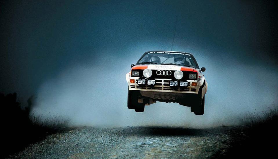 """<p style=""""text-align: center;""""><strong>Audi Sport Quattro </strong>дебютировал на Женевском автосалоне 3 марта 1980 года и стал первым раллийным автомобилем, ради которого правила были изменены. Sport Quattro было позволено участвовать в заездах с четырьмя ведущими колесами. Это решение стало переломным моментом для автоспорта и открыло золотую эру побед Audi в мировых чемпионатах.</p> <p style=""""text-align: center;""""><strong></strong></p>"""